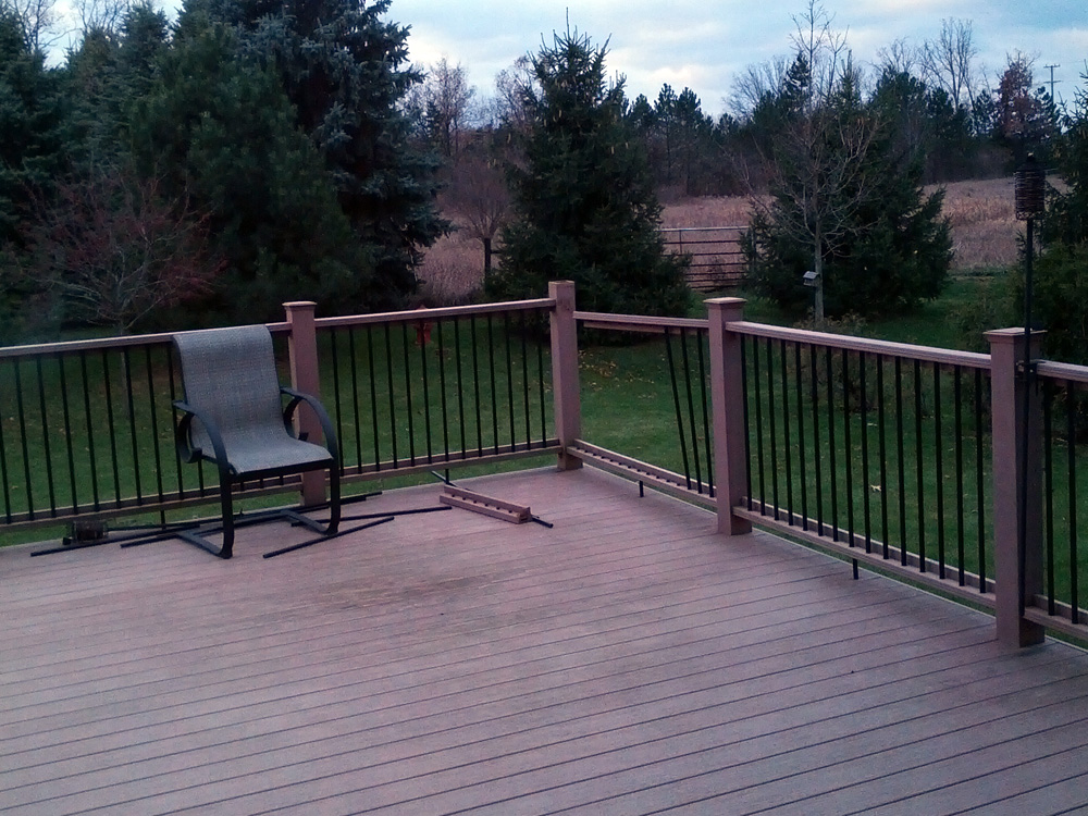 A look at our damaged deck, with the railing broken, a post cap missing, and balusters strewn around.